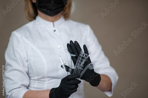 a beautician in black medical gloves holds nozzles for the darsonval apparatus Wallpaper Mural