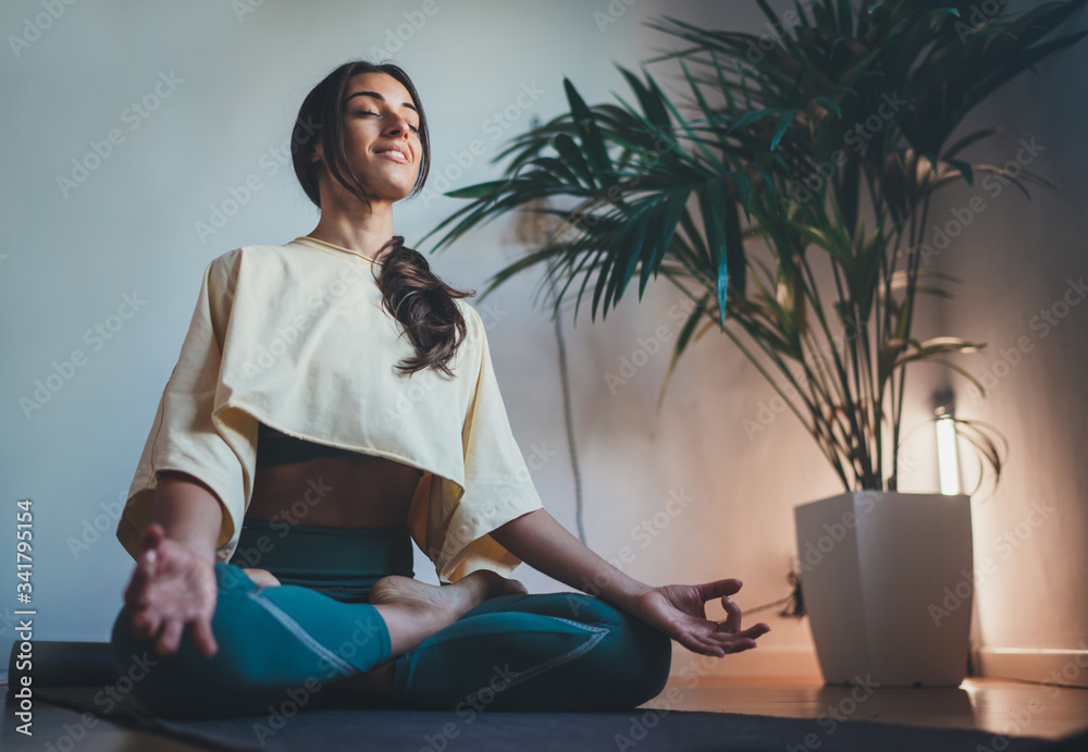 Fototapeta Young happy beautiful woman in cozy cropped sweatshirt and leggings practicing yoga at home sitting in lotus pose on yoga mat meditating smiling relaxed with closed eyes Mindfulness meditation concept