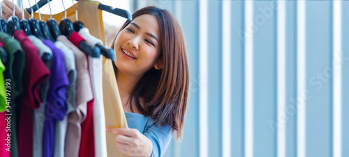 Young Asian woman buying and choosing clothes in a shop store happily with space for text Tablou Canvas