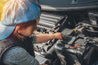 Little child trying to fix broken real car. Dreaming to be auto technician. View from the back