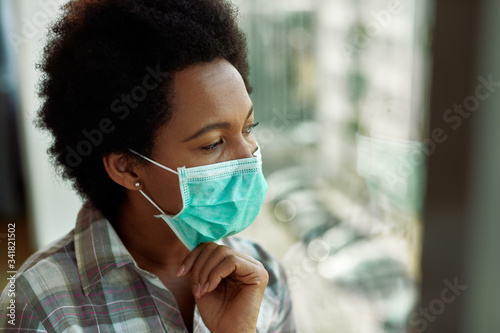 Photo Thoughtful African American woman with face mask by the window.