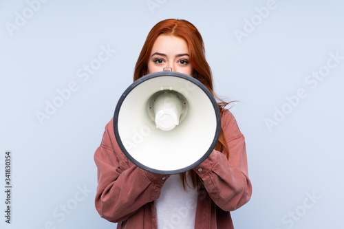 Fotografija Redhead teenager girl over isolated blue background shouting through a megaphone