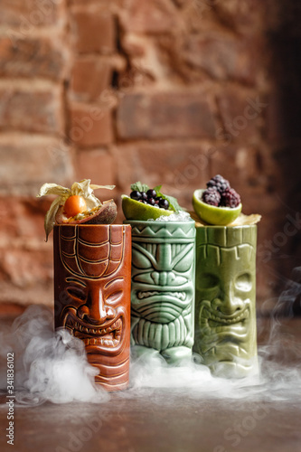 Photo Variety beverages Mexican tequila fruity flavors in an artistic glassware with smoky effect bricks background