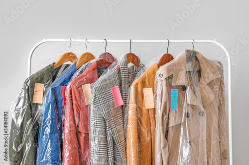 Fotografia, Obraz Rack with clothes after dry-cleaning on light background