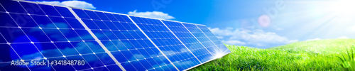Fototapeta Banner Of Solar Panels In Green Grass Landscape With Blue Sky And Sunlight - Clean Energy Concept obraz
