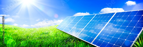 Fototapeta Solar Panels In Green Grass Landscape With Blue Sky And Sunlight - Clean Energy Concept obraz