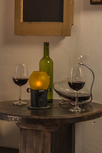 Red Wine Glass In Front Of An Empty Green Bottle And Crystal Wine Container With Old Lamp Over Dark Wood Table