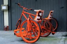 Vintage Orange Tandem Bicycle Against Wall