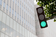 Low Angle View Of Green Light Against Modern Office Building In City