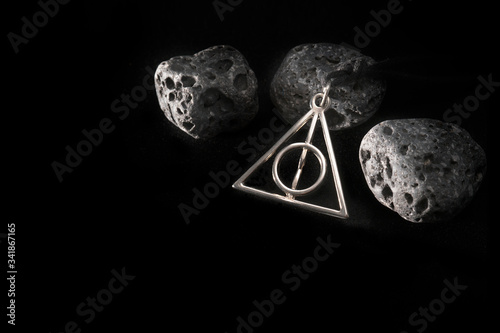 Carta da parati Angels Necklace of Amulets,Wizards amulet and Black lava rock on black, Wizard tool