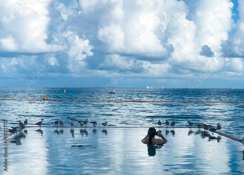 Serene view with woman, birds, city in distance, clouds, ocean, infinity pool, b Canvas Print