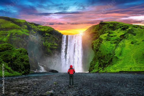 Skogafoss waterfall in Iceland. Guy in red jacket looks at Skogafoss waterfall. - 341875754