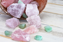 A Close Up Image Of A Tipped Over Pottery Bowl Filled With Rose Quartz And Green Aventurine Cyrstals.