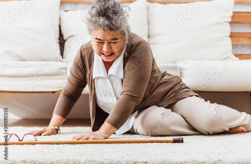 Cuadros en Lienzo Asian senior woman falling down lying on floor at home alone