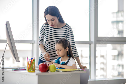 Fotografie, Tablou Dark-haired mom and daughter doing lessons together
