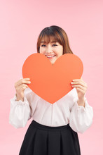 Cute Asian Woman Holding Red Heart Isolated On Pink