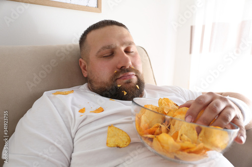 Photo Lazy overweight man with chips sleeping on sofa at home, closeup