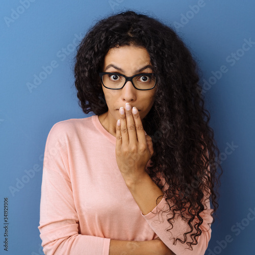 Shocked young woman with her hand to her mouth Canvas Print