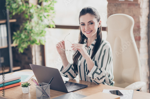 Fototapeta Portrait of positive cheerful chief company owner girl sit desk hold her spectacles ready welcome her startup development partners in modern workstation obraz