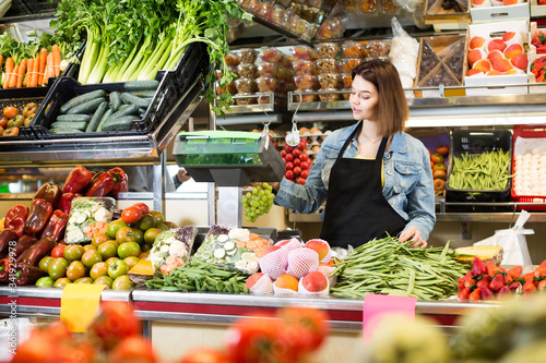 Fotografía shopping assistant weighing fruit and vegetables in grocery shop