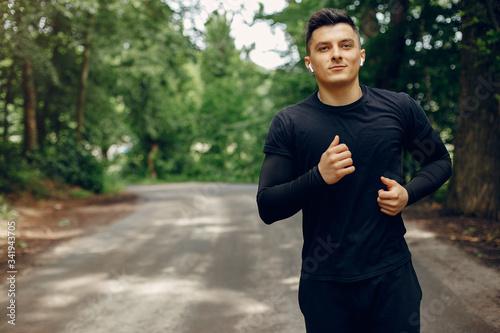 Fotografía Handsome man in a park. Sportsman in a sportswear. Guy training