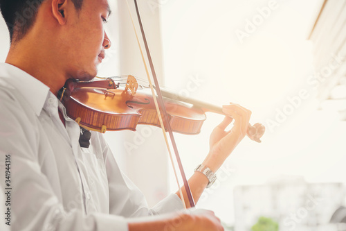 Fototapeta A musician man in white shirt is practicing the violin playing with the melodiousness