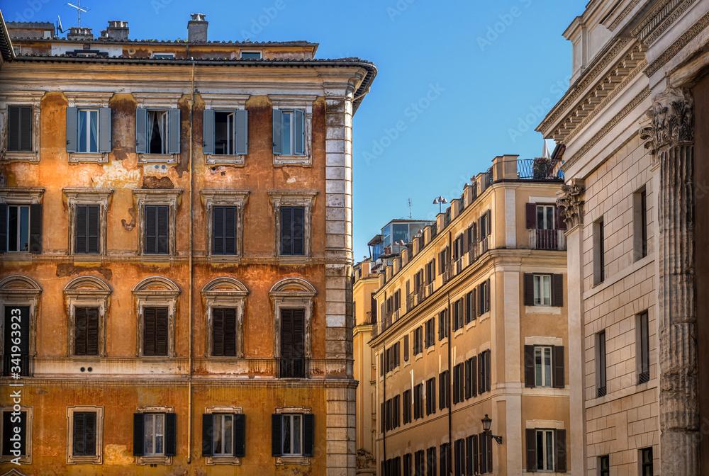 Fototapeta Widok na zabytkowe kamienice w centrum Rzymu, Włochy. Piękne błękitne niebo kontrastuje z kolorowymi fasadami budynków