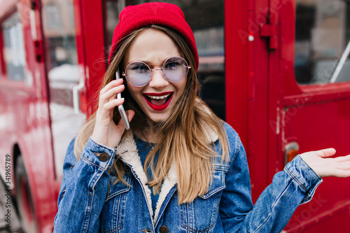 Photo Beautiful girl in red hat expressing amazement while talking on phone