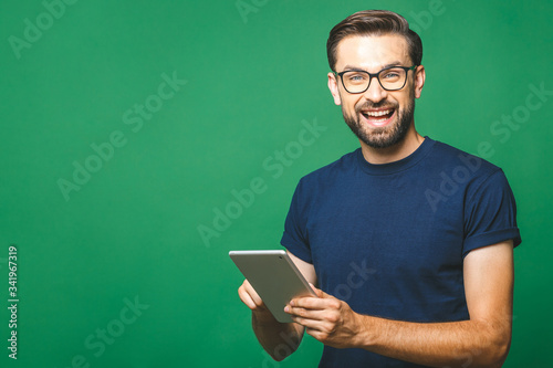 Fototapeta Happy young man in casual shirt and glasses standing and using tablet over green background obraz
