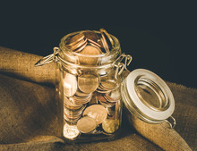 Close-up Of Coins In Jar On Ta...