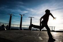 Full Length Of Silhouette Boy Running On Navigational Compass Against Sky