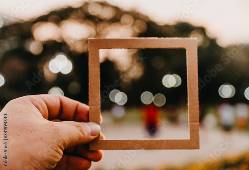 Cuadros en Lienzo Hand holding blank paper frame with nature bokeh background