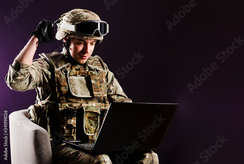 Fotomural Man gamer with laptop is celebraiting the win in soldier clothes on brown background