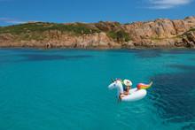 Woman Sitting On Inflatable Unicorn In Aegean Sea Against Sky