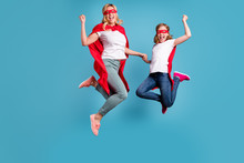 Full Length Photo Of Funny Mom Lady Little Daughter Spend Time Together Superhero Win Costume Competition Jump High Up Wear S-shirts Red Coat Masks Isolated Blue Color Background