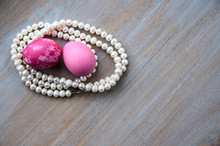 Two Easter Eggs Painted In Red And Pink Paint Lie In The Corner Of A Vintage Wooden Tabletop Among The Rings Of A White Pearl Necklace. Day, The Table Is Lit By Solar Light