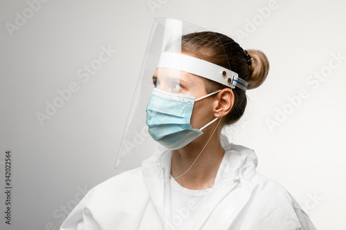 young female doctor in medical mask and protective shield on her head looking away Wallpaper Mural