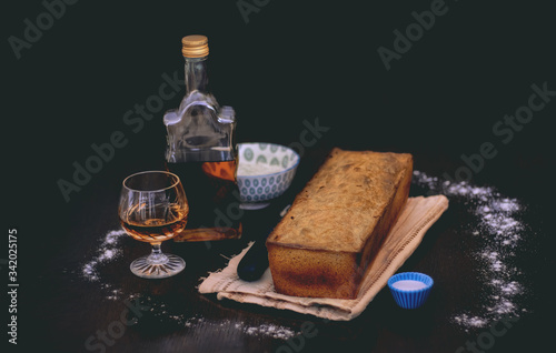 Fresh bread with salt and flour accompanied by glass and bottle of brandy on dar Wallpaper Mural
