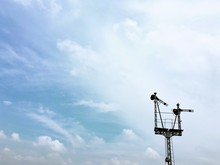 Low Angle View Of Railway Signal Against Cloudy Sky
