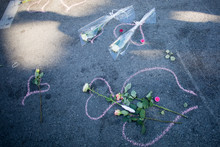 High Angle View Of Bouquets And Tea Lights On Chalk Drawing At Road After Terrorist Attack