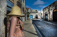 Mannequin Wearing Hat On Sidewalk Amidst Buildings