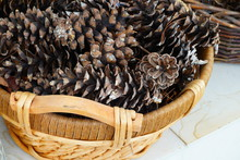Basket Of Pine Cones By The Fireplace
