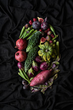 Top View Of Basket With Assorted Colorful Fresh Fruits And Vegetables Including Pomegranate And Plums And Figs With Mini Eggplants And Sweet Potato On Black Background