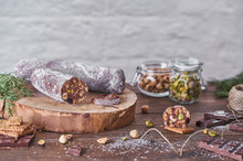 Traditional Homemade Chocolate Salami With Hazelnuts And Pistachios On Wooden Board Placed On Table With Ingredients And Green Spruce Branches