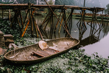 From Above Of Old Wooden Fishing Boat And Asian Hat On Rocky Coast Near Wooden Old Bridge In Vietnam