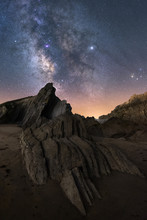 From Below Of Rough Cliff Peak Under Milky Way Colorful Blue Night Sky And Shiny Stars On Background