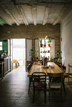 Large Wooden Table And Chairs In Rustic Retro Styled Bar With Shabby Ceiling And Potted Green Plants On Window