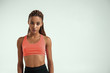 Sporty and healthy. Young african woman in sportswear standing against grey background and looking at camera