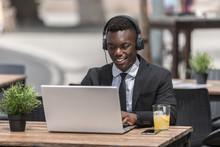 Black Man In Suit Sitting In C...