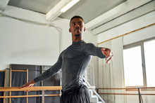 Professional Ballet Dancer Looking Away While Training In A Modern Studio Using Wooden Handrail